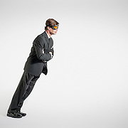 A business portrait of a main wearing flying goggles and leaning at an almost impossible angle.
