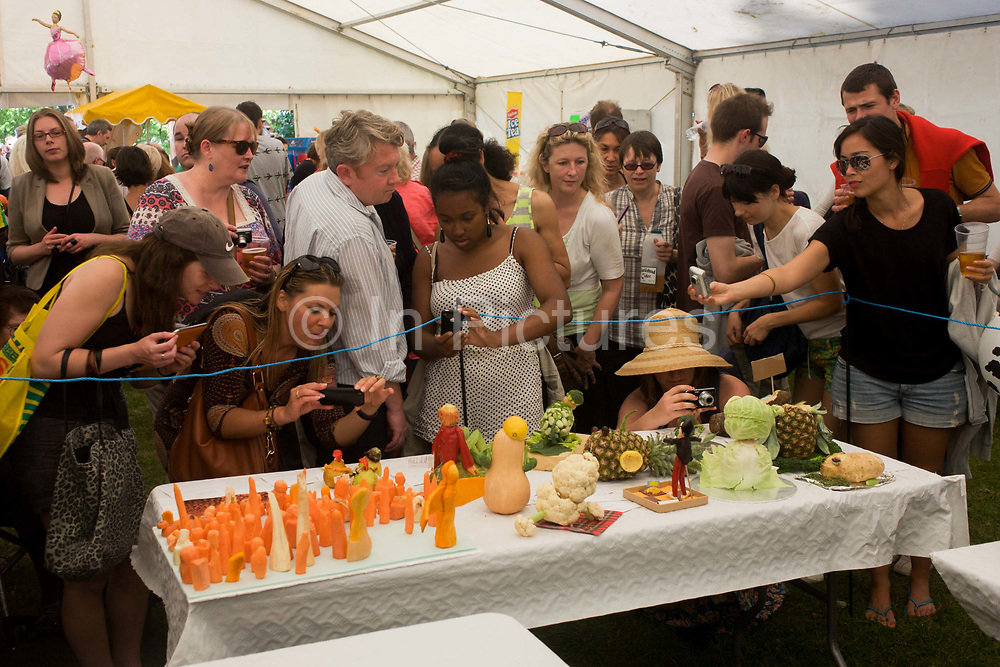 Locals admire carved vegetables on a small table inside a marquee at Lambeth Country Show. Housed in the tent, are gathered this group of south Londoner, here to admire and marvel at the collection of organic matter: Pineapples, potatoes, squashes and cabbages that have been carved and shaped into various artistic forms for judging then for the delight of these woman. They hold out smartphones to photograph and admire further, getting right down to table level for a closer picture.