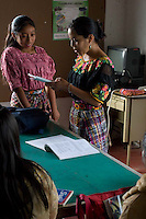 Nirma Angélica Calel Aean (right) teaches young laborers, who work for local vegetable and fruit exporters, textile plants and private homes, primary school subjects at the Centro de Estudios Apoyo al Desarrollo Local in Chimaltenango, Guatemala on Sunday, March 11, 2007. The workers' long hours keep them from studying much during the week.