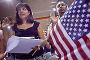 """04 JULY 2009 -- PHOENIX, AZ:  MIRIAM WHITE, originally from Colombia, takes the oath of citizenship to become a US citizen in Phoenix, AZ, July 4. U.S. Citizenship and Immigration Services and South Mountain Community College in Phoenix, AZ, hosted the 21st annual """"Fiesta of Independence"""" Saturday, July 4. More than 180 people from 58 countries took the US Oath of Citizenship and became naturalized US citizens. The ceremony was one of dozens of similar ceremonies held across the US this week. USCIS said more than 6,000 people were naturalized US citizens during the week.  Photo by Jack Kurtz / ZUMA Press"""