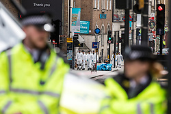 © Licensed to London News Pictures. 05/06/2017. London, UK. Forensics officers are seen through two police officers near Borough Market. Three attackers drove a van at pedestrians before stabbing a number of people in nearby bars on the evening of Saturday 3 June 2017 in what police have described as a terrorist attack. Photo credit: Rob Pinney/LNP