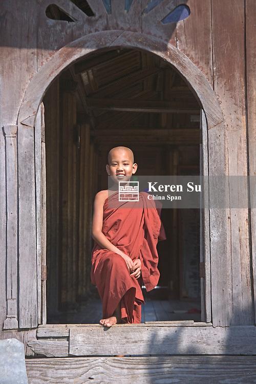 Monk by the oval window at Shwe Yaunghwe Kyaung Monastery, Nyaungshwe, Myanmar