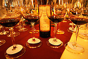 A bottle of Preludio Barrel Select 1998 Lote Number 42 Region Juanico and a glass of the same wine at dining and tasting table filled with glasses. Glasses with a vertical selection of different vintages to compare in tasting. Bodega Juanico Familia Deicas Winery, Juanico, Canelones, Uruguay, South America