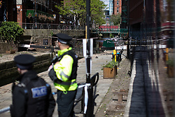 © Licensed to London News Pictures . 14/05/2020 . Manchester , UK . Police stand close to a barge by a taped off section of towpath on the Rochdale Canal , parallel with Canal Street in Manchester City Centre . GMP report they've arrested four men after a woman was raped last night (13th/14th May 2020) . Photo credit : Joel Goodman/LNP