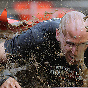 Expressions of competitors as they tackle the mud pit during the New York Merrell Down and Dirty Obstacle Race presented by Subaru. Over 6000 competitors took part in the event which included mud pits, water crossings, slippery mountain, cargo nets, monster climb and ladder walls. The event was held at Pelham Bay Park The Bronx, New York. 29th September 2013. Photo Tim Clayton