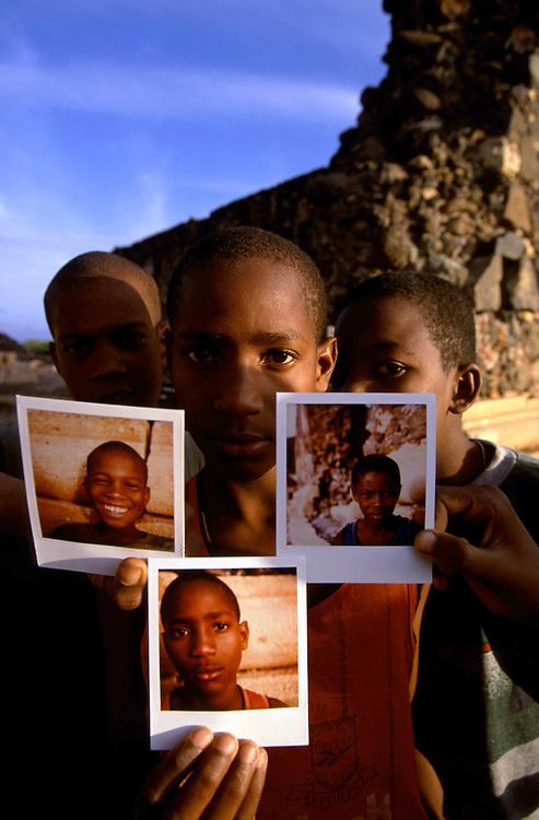 Children photographed with their Polaroids next to the Cidade Velha Basilica's ruins.