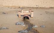 Drainage pipe emptying water onto sandy beach, Felixstowe, Suffolk, England