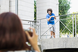 Woman taking photograph of man standing on bridge