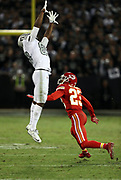 A defender falls down as Oakland Raiders wide receiver Amari Cooper (89) leaps in the air while trying to catch a pass while covered by Kansas City Chiefs cornerback Phillip Gaines (23) during the 2017 NFL week 7 regular season football game against the Kansas City Chiefs, Thursday, Oct. 19, 2017 in Oakland, Calif. The Raiders won the game 31-30. (©Paul Anthony Spinelli)