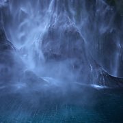 The spectacular Stirling Falls on Milford Sound..Milford Sound (Piopiotahi in Ma¯ori) is a fjord in the south west of New Zealand's South Island, within Fiordland National Park and the Te Wahipounamu World Heritage site. It has been judged the world's top travel destination and is acclaimed as New Zealand's most famous tourist destination..Milford Sound runs 15 kilometres inland from the Tasman Sea at Dale Point - the mouth of the fiord - and is surrounded by sheer rock faces that rise 1,200 metres (3,900 ft) or more on either side. Among the peaks are The Elephant at 1,517 metres (4,977 ft), said to resemble an elephant's head and The Lion, 1,302 metres (4,272 ft), in the shape of a crouching lion. Lush rain forests cling precariously to these cliffs, while seals, penguins, and dolphins frequent the waters and whales can be seen sometimes..Milford Sound sports two permanent waterfalls all year round, Lady Bowen Falls and Stirling Falls. After heavy rain many hundreds of temporary waterfalls can be seen running down the steep sided rock faces. .The beauty of this landscape draws thousands of visitors each day, with between 550,000 and 1 million visitors in total per year. This makes the sound one of New Zealand's most-visited tourist spots, and also the most famous New Zealand tourist destination.  Milford Sound, New Zealand. 29th April 2011. Photo Tim Clayton