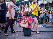 """31 DECEMBER 2012 - BANGKOK, THAILAND: People pray at the Erawan Shrine at the Ratchaprasong Intersection on New Year's Eve. The traditional Thai New Year is based on the lunar calender and is celebrated in April, but the Gregorian New Year is celebrated throughout the Kingdom, especially in larger cities and tourist centers, like Bangkok, Chiang Mai and Phuket. Many Thais go to Buddhist temples and shrines to """"make merit"""" for the New Year. The Bangkok Countdown 2013 event was called ?Happiness is all Around @ Ratchaprasong.? All of the streets leading to Ratchaprasong Intersection were closed and the malls in the area stayed open throughout the evening.    PHOTO BY JACK KURTZ"""