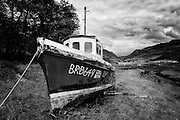 Loch Long (Highlands) os a sea loch located on the North West Coast of Scotland, not far from Eilean Donan Castle.<br /> <br /> This photograph is a monochramatic version of a boat on the shore of Loch Long, North West Coast of Scotland. The photograph can be purchased as print, mounted print in frames, canvas or aluminum or as a digital file.