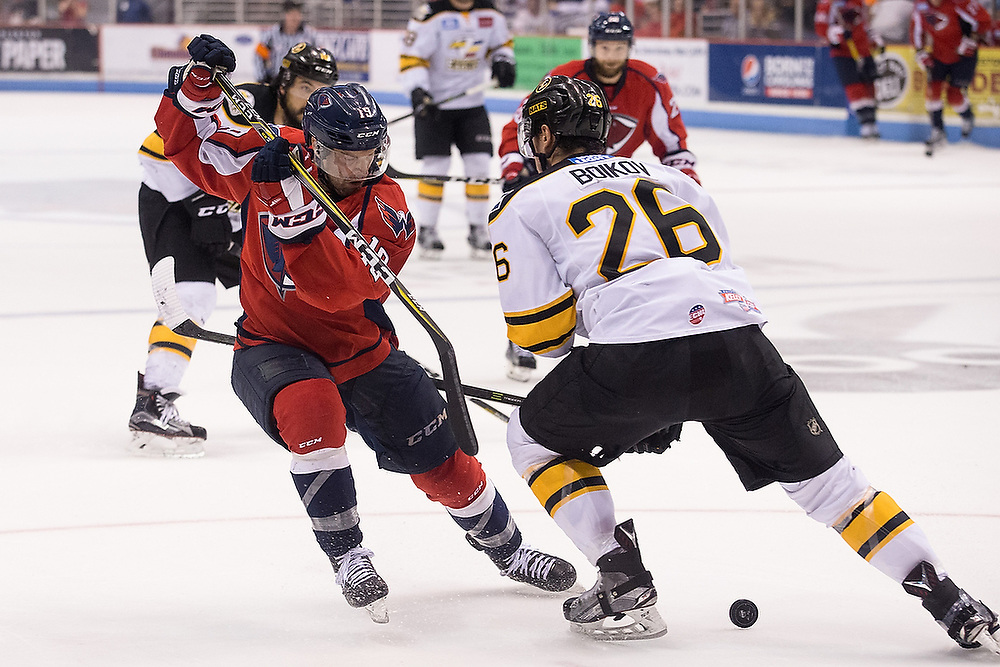 South Carolina's Kelly Zajac (19) pushes the puck through the legs of Colorado's Sergei Boikov (26). <br /> Colorado Eagles vs. South Carolina Stingrays in Game 4 of the Kelly Cup Finals at North Charleston Coliseum in Charleston, S.C. on Monday, June 5, 2017.<br /> Zach Bland Photo