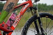 Mountain bike splashing through a muddy puddle