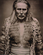 Portrait of an old caucasian man who wears an ethnic costume made of fur.