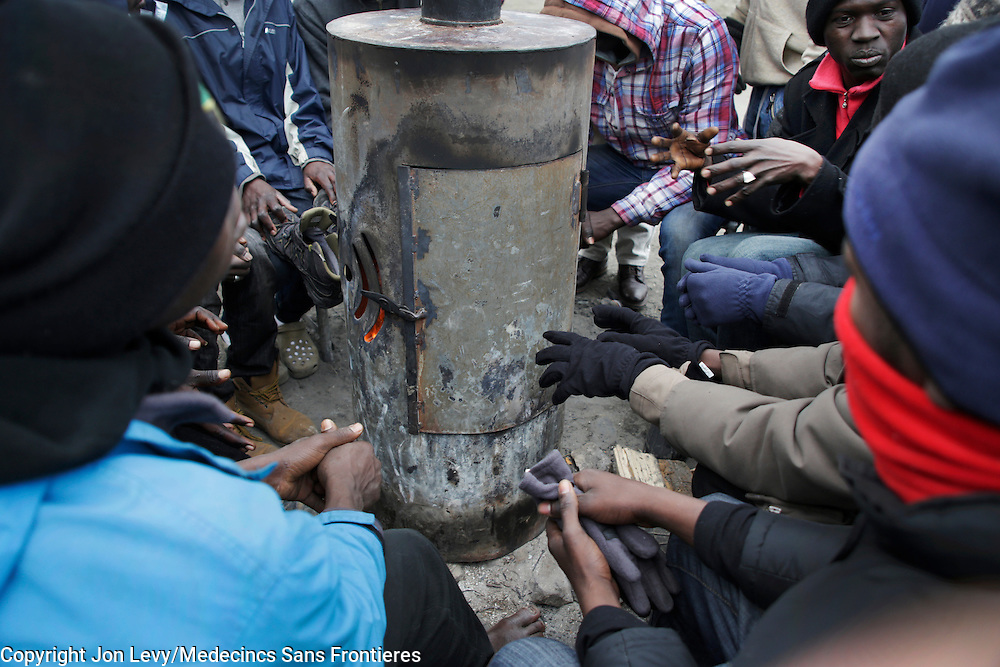 Refugees in the Calais refugee camp in northern France warm their hands with the heat from a wood-burning stove. <br /><br />Calais: AA Gill visits the refugee camps of Calais and Grande Synthe in Dunkirk.