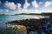 Saffron Cove on the west coast of Tresco. Plumb Island, Cromwell's Castle and the island of Bryher are all in view. Isles of Scilly, Cornwall, UK.