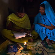 CAPTION: Chandravati (right), herself illiterate, makes an effort to learn from her school-going daughter Pinki (left) after dark in Baharayen. For now, this means considerable eye strain in the dark, as the room is lit only by burning dangerous kerosene. Home lighting through SPEED will put an end to these challenges. LOCATION: Baharayen, Faizabad District, Uttar Pradesh, India. INDIVIDUAL(S) PHOTOGRAPHED: From left to right - Pinki and Chandravati.