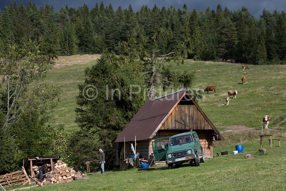 Agricultural workers chop wood in front of a traditional Polish shepherds hut on the hillside, on 20th September 2019, Biala Woda, Jaworki, near Szczawnica, Malopolska, Poland.