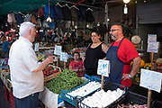 Market stalls, stallholders and customers at the famous Ballero street market for vegetables and other fresh food in Palermo, Sicily, Italy