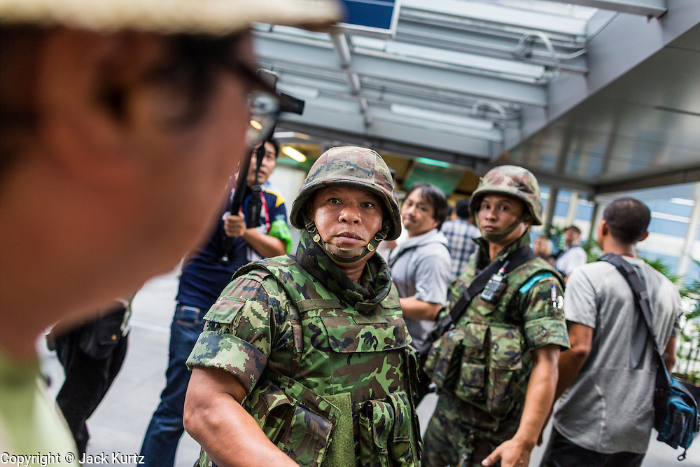 """01 JUNE 2014 - BANGKOK, THAILAND: Thai soldiers patrol the Asok BTS Skytrain station in Bangkok after a flash mob protested against the coup near the station. The Thai army seized power in a coup that unseated a democratically elected government on May 22. Since then there have been sporadic protests against the coup. The protests Sunday were the largest in several days and seemed to be spontaneous """"flash mobs"""" that appeared at shopping centers in Bangkok and then broke up when soldiers arrived. Protest against the coup is illegal and the junta has threatened to arrest anyone who protests the coup. There was a massive security operation in Bangkok Sunday that shut down several shopping areas to prevent the protests but protestors went to malls that had no military presence.    PHOTO BY JACK KURTZ"""