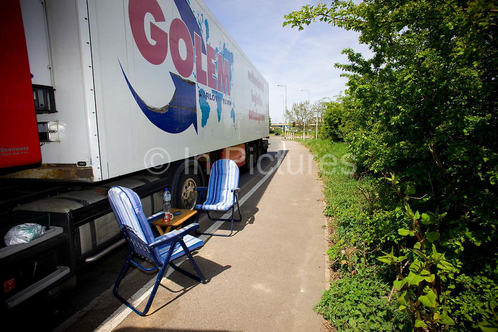 A couple working for a European long haulage company take a break at a roadside layby on the A10. While the husband rests in his cab, the wife sets up a picnic in the layby on the 27th April 2010 in Kings Lynn in the United Kingdom.