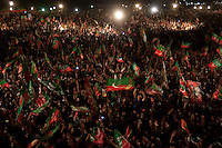 Supporters of Imran Khan, chairman of the Pakistan Tehreek-e-Insaf wave flags and cheer as he speaks from the stage during an election campaign rally in Faisalabad, Pakistan, Sunday, May 5, 2013. Pakistan is scheduled to hold parliamentary elections on May 11, the first transition between democratically elected governments in a country that has experienced three military coups and constant political instability since its creation in 1947.