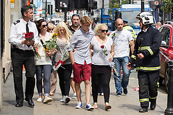 © Licensed to London News Pictures . FILE PICTURE DATED 15/07/2013 . Oldham Street , Manchester , UK . Stephen Hunt's family arrive at the scene . Son Sam (maroon shorts , 15), brother Christopher (white t-shirt, jeans, close cropped hair), grandmother Ruth (blue check shirt, dark trousers , red sunglasses), mother Susan (blue top, beige slacks, sunglasses), stepfather Wilf (dark hair, black t-shirt, grey shorts), daughter Charlotte (black and white sleeveless top, black pants, 18), sister Sarah (cream sleeveless top, blue jeans, dark hair, sunglasses) and ex-wife Zoe (white top, black pants, sunglasses) . The scene on Oldham Street following a fire at Paul 's Hair World on 13th July which claimed the life of fireman Stephen Hunt . Photo credit : Joel Goodman/LNP