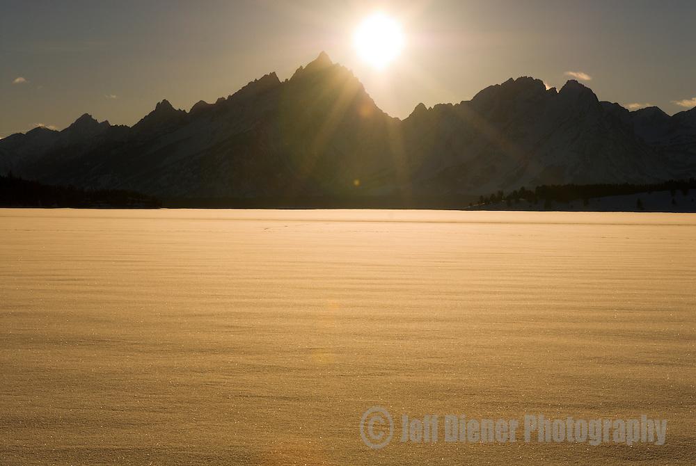 The Teton Range rises above a snow covered Jackson Lake in Grand Teton National Park, Jackson Hole, Wyoming.