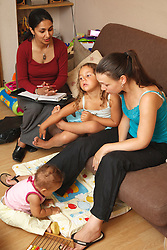 Social worker with young mother and children.