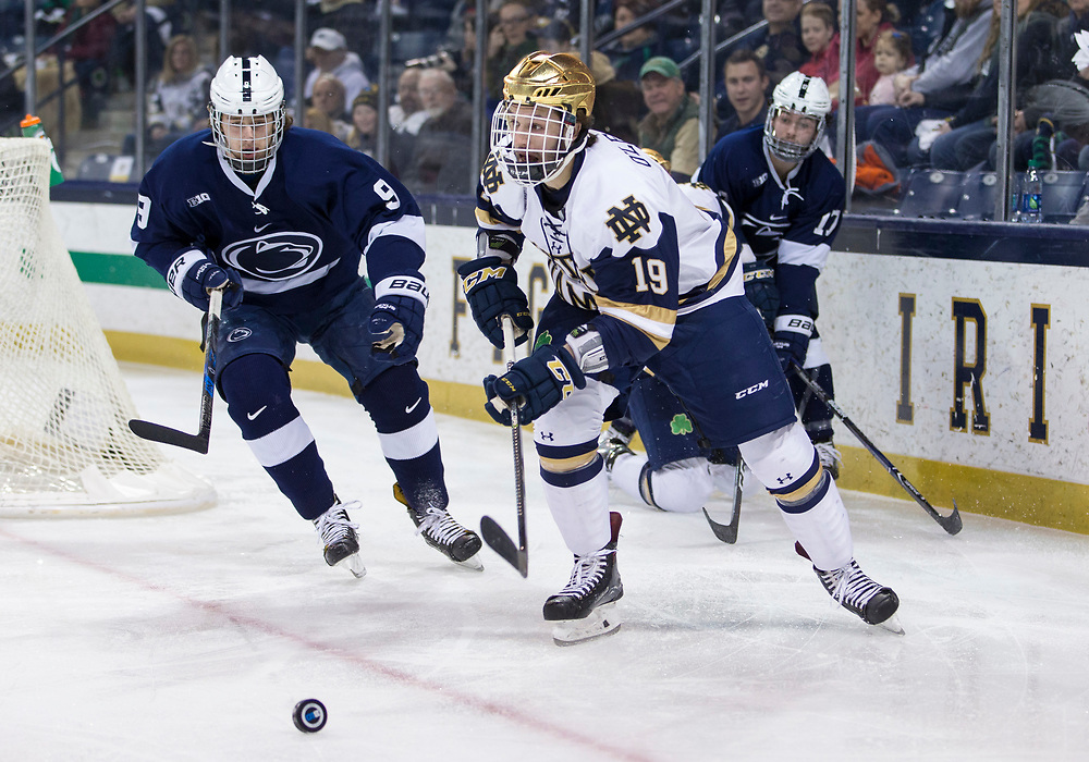 March 10, 2018:  Notre Dame forward Mike O'Leary (19) controls the puck as Penn State forward Alex Limoges (9) back checks during NCAA Hockey game action between the Notre Dame Fighting Irish and the Penn State Nittany Lions at Compton Family Ice Arena in South Bend, Indiana.  Notre Dame defeated Penn State 3-2.  John Mersits/CSM
