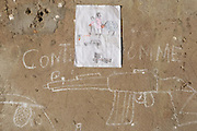 Drawing of family and daily scenes next to drawings of guns on the wall of a transit and orientation center for child soldiers in N'Djamena, Chad on Thursday June 10, 2010.