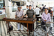 A Marimba band performs inside the iconic Gran Café de La Parroquia along the Malecon in Veracruz City, Mexico. The cafe is known for their long pours of hot milky coffee known as a lechero which they have served since 1808 and in their current form has operated continuously since 1926.