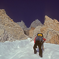 A mountaineer ascends the Palisade Glacier towards Clyde's Couloir that divides 14,249-foot North Palisade (summit hidden on left) and 14,200-foot Starlight Peak (right,) a classic climb in California's Sierra Nevada.
