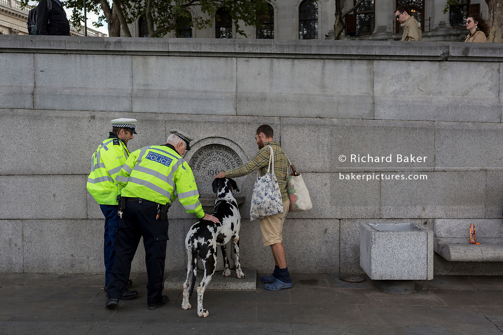 Two Met Police officers admire a Great Dane, the pet of an environmental activist drinking from a public fountain, while protesting about Climate Change during an occupation of Trafalgar Square in central London, the third day of a two-week prolonged worldwide protest by members of Extinction Rebellion, on 9th October 2019, in London, England.