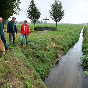 """Nederland Kronenberg 30 september 2008 20080930 Foto: David Rozing ..Serie vernattingscampagne """" Nieuw Limburgs Peil """" de Peel .Hond van boer Jan van der Sterren bij watergang. . Vernattingscampagne """" Nieuw Limburgs Peil """" in omgeving de Peel, uitgevoerd door o.a. de  plaatselijke boeren in samenwerking met het waterschap Peel en Maasvallei. Het doel is een hoger peil van het grondwater dmv het vasthouden van hemelwater. Dit  wordt verwezenlijkt door de aanleg van stuwen in de watergangen bij bv akkers. Door de stuwen in de sloten/ watergangen dicht te zetten wordt het grondwaterpeil hoger in het gebied. Voordelen hiervan zijn: verdroging van de natuur wordt tegen gegaan, voor de boeren kan het drie beregeningen per jaar besparen. Boerenpeil: 400 van de inmiddels 1250 stuwen worden beheerd door de boeren. Natuurgebieden als De Grote Peel en Maria peel hebben veel te lijden gehad onder eerder .waterbeheer:  Het waterschap heeft in het verleden veel akkerslootjes, beken en kanaaltjes aangelegd om ervoor te zorgen dat het water rond dit natuurgebied snel kon wegvloeien, zodat de oogsten.niet zouden verrotten en de akkers goed bewerkbaar waren, maar waardoor nu het waterpeil erg snel zakt..Medewerkers van het waterschap bezoeken de boeren thuis en voeren keukentafelgesprekken met hen om ze te betrekken bij het project. .De Peel is een grotendeels verdwenen hoogveengebied op de grens van de Nederlandse provincies Noord-Brabant en Limburg. ..Foto David Rozing"""