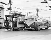 """Y-480203A. Portland Transit Co. old & new.  On left is PT trolley 417 with AB marking, indicating Alberta St. line. On right is new bus #910 with Irvington Sign. Building on left is at NE 29th & Alberta. February 3, 1948.  This photo was published in the Portland Transit Co.'s 1947 Annual Report (which was published in 1948). Caption: """"Walt Baker, trolley skipper since 1911, greets Merrit Lutman, pilot of new Mack bus"""" (The restaurant on the left is now Bernie's Southern Bistro)"""