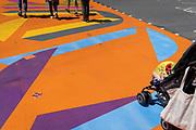 A child is pushed over the road holding a retail souvenir, on the multi-coloured markings of a crossing at Piccadilly Circus, on 16th July 2021, in London, England.