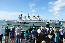 © Licensed to London News Pictures. File pic dated 12/08/2013. London, UK. HMS Illustrious returning to Portsmouth in August 2013. The government has announced that HMS Illustrious is heading to the Philippines to help with the Typhoon Haiyan recovery efforts. Photo credit : Bryan Moffat/LNP