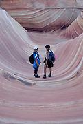 "Tourist walking through the beautiful rock formation ""The wave"", Vermillion Cliffs, Utah, USA, MR"