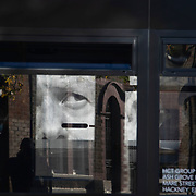 A billbord poster with an image of Prime Minister Boris Johnson and the word SHAME November 4th 2020 in Hackney, London, United Kingdom. The artwork is by the artist Subvertiser. The poster is seen through a bus.