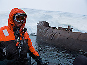 A whaling shipwreck rusts in the Southern Ocean near a white glacier on an island offshore from the Antarctic Peninsula.
