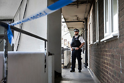 © Licensed to London News Pictures. 01/07/2020. London, UK. A police officer guards a block of flats in Monarch Parade in Mitcham, south London after a four year old girl was found seriously injured yesterday. She was taken to hospital where she later died. A woman, aged 35, is fighting for her life after she was also found suffering serious injuries inside the property. Photo credit: Peter Macdiarmid/LNP