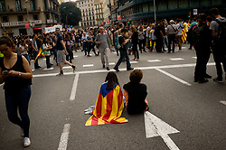 October 3, 2017 - Barcelona, Catalonia, Spain - A girl wrapped with a estelada flag sits on the ground of the streets of Barcelona. A general strike goes over Catalan territory to protest against brutality by police during a referendum on the region's secession from Spain that left near nine  hundred of people injured. (Credit Image: © Jordi Boixareu via ZUMA Wire)