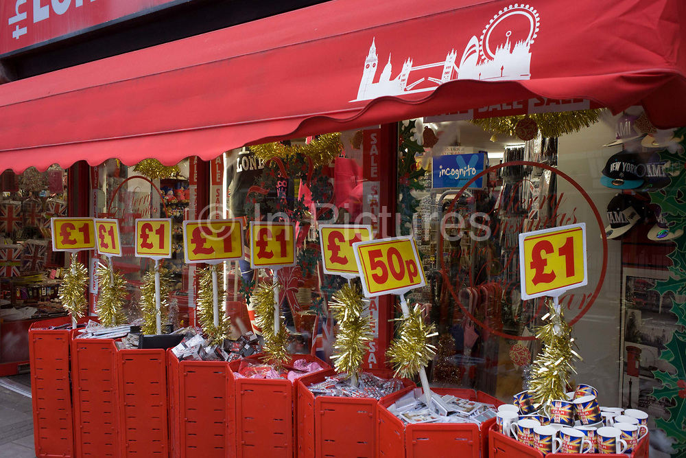 Tacky Christmas tourist trinkets on sale outside a discount shop in New Oxford Street in central London. Sold for a Pound £1 or for 50 pence are the products made to entice the public into spending their money on sub-standard goods. We see mugs and pens etc. in red plastic bins beneath a red canopy.