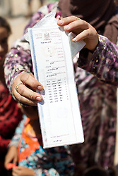 © Licensed to London News Pictures. 27/07/2014. Erbil, Iraq. A refugee from southern Iraq holds up her family's ration card at a camp for internally displaced persons (IDP's) at the Kalak Checkpoint near Erbil in Iraqi-Kurdistan. © Licensed to London News Pictures.