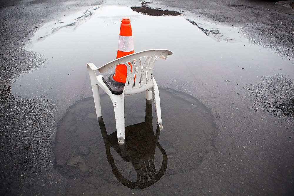 A plastic lawn chair and orange traffic cone warn of a large, flooded hole in the pavement of a hotel parking lot in Valdez, Alaska.