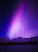 Purple and blue aurora above the Talkeetna Mountains and Colorado Lake with subtle blue light of the approaching dawn, geomagnetic storm on March 31, 2001, Broad Pass, Alaska.