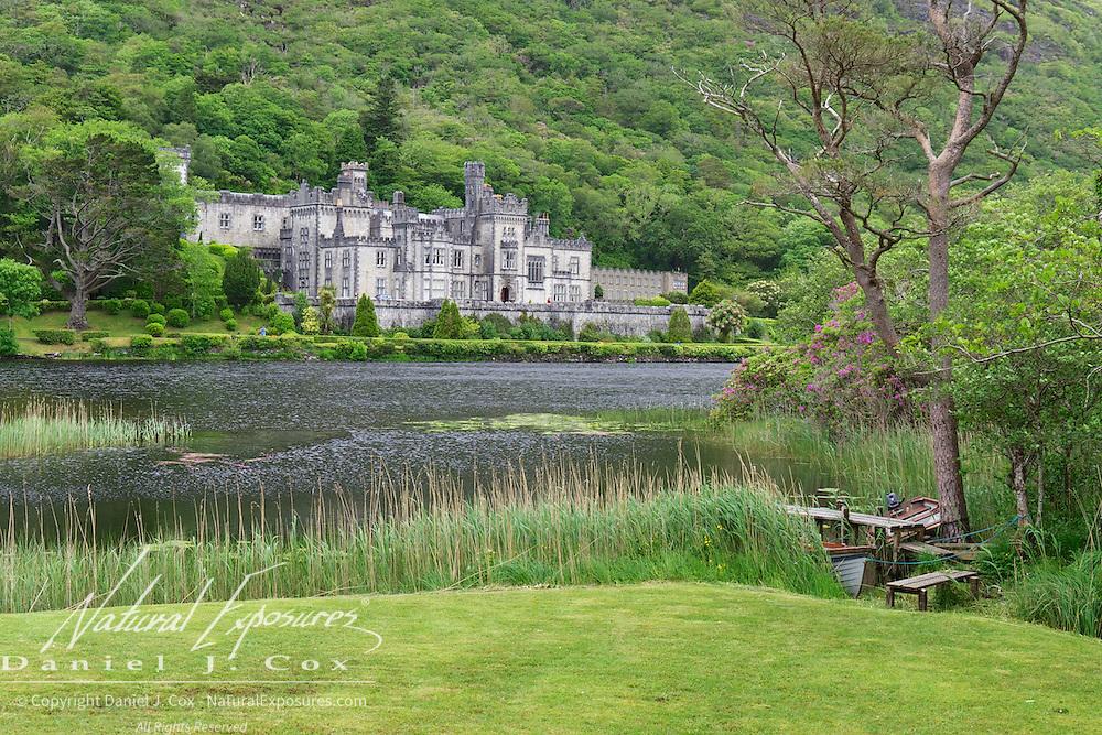 Small boats at the grassy edge of the lake of Kylemore Abbey, Ireland