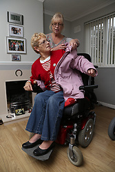 Carer putting Wheelchair user's coat
